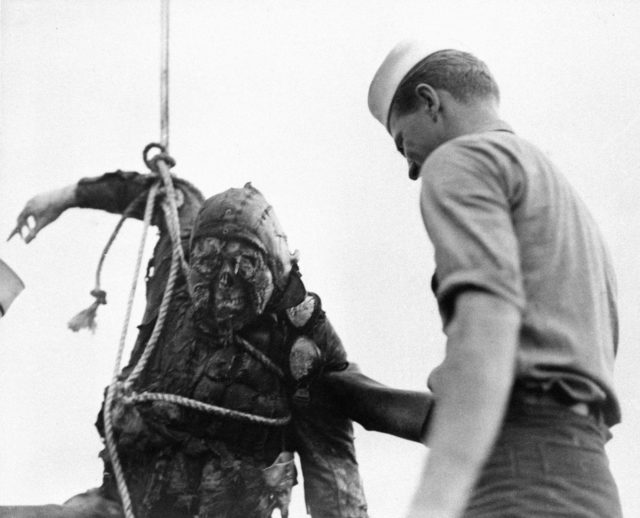 An American Seaman looks at the charred corpse of a Japanese flier brought up from the bottom of Pearl Harbor where he crashed with his burning plane during the Japanese attack on Dec. 7, 1941 in Hawaii.